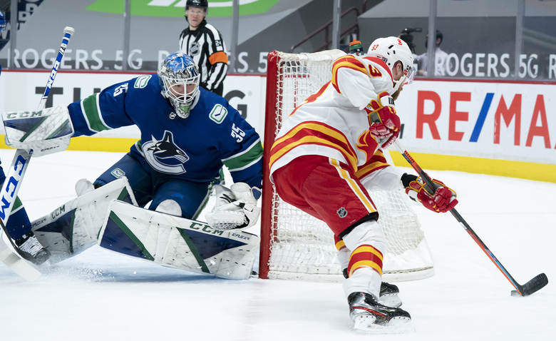 Calgary Flames center Sam Bennett (93) tries to get a shot past Vancouver Canucks goaltender Thatcher Demko (35) during the first period of an NHL hockey game Thursday, Feb. 11, 2021, in Vancouver, British Columbia. (Jonathan Hayward/The Canadian Press via AP)