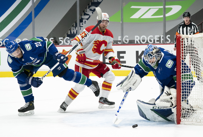 Vancouver Canucks defenseman Alexander Edler (23) tries to stop Calgary Flames center Sam Bennett (93) from getting a shot on Canucks goaltender Thatcher Demko (35) during the first period of an NHL hockey game Thursday, Feb. 11, 2021, in Vancouver, British Columbia. (Jonathan Hayward/The Canadian Press via AP)