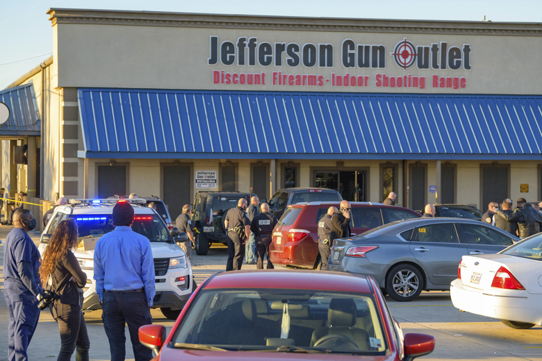 Bystanders react at the scene of a multiple fatality shooting at the Jefferson Gun Outlet in Metairie, La., Saturday, Feb. 20, 2021. A suspect fatally shot two people at a gun store in a suburb of New Orleans on Saturday afternoon, and the shooter also died during gunfire as others engaged the suspect both inside and outside the outlet, authorities said. (AP Photo/Matthew Hinton)