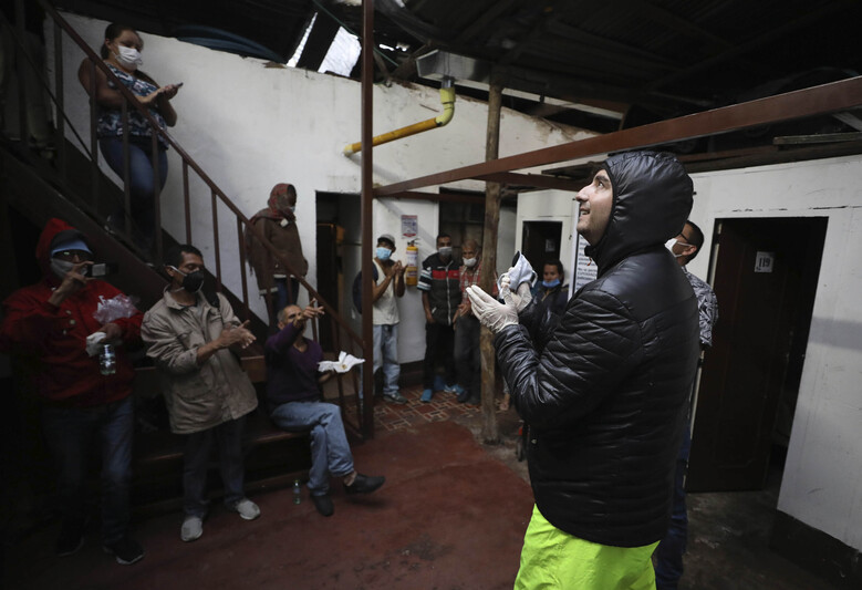 FILE – In this March 30, 2020 file photo, Emiliano Moscoso, right, talks to Venezuelan and Colombian people in a boarding house in Bogota, Colombia.  Moscoso recently launched a program called Solidarity Menu to feed people in need during the coronavirus outbreak. (AP Photo/Fernando Vergara, File)