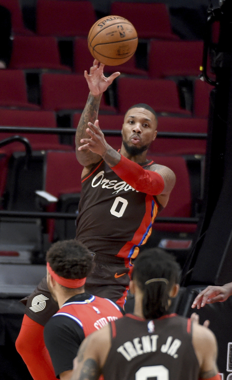 Portland Trail Blazers guard Damian Lillard passes the ball during the first half of the team's NBA basketball game against the Philadelphia 76ers in Portland, Ore., Thursday, Feb. 11, 2021. (AP Photo/Steve Dykes)