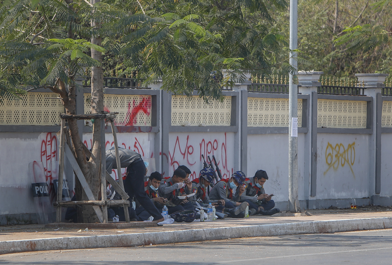 Police officers eat a meal along a sidewalk near a graffiti against the recent military coup in Mandalay, Myanmar, Friday, Feb. 12, 2021. Myanmar's coup leader used the country's Union Day holiday on Friday to call on people to work with the military if they want democracy, a request likely to be met with derision by protesters who are pushing for the release from detention of their country's elected leaders. (AP Photo)