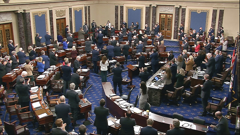 In this image from video, senators and staff give a standing ovation to U.S. Capitol Police offer Eugene Goodman, standing in the far back row, shortly before voting to award him the Congressional Gold Medal for his actions during the Jan. 6 riot, as the Senate took a break from the second impeachment trial of former President Donald Trump in the Senate at the U.S. Capitol in Washington, Friday, Feb. 12, 2021. (Senate Television via AP)