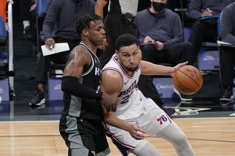 Philadelphia 76ers guard Ben Simmons, right, drives against Sacramento Kings guard Buddy Hield, left, during the first half of an NBA basketball game in Sacramento, Calif., Tuesday, Feb. 9, 2021. (AP Photo/Rich Pedroncelli)
