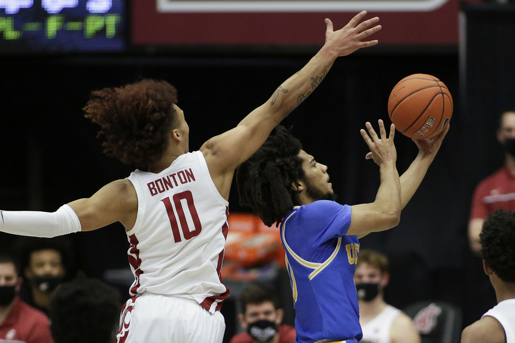 UCLA guard Tyger Campbell, right, shoots next to Washington State guard Isaac Bonton during the first half of an NCAA college basketball game in Pullman, Wash., Thursday, Feb. 11, 2021. (AP Photo/Young Kwak)