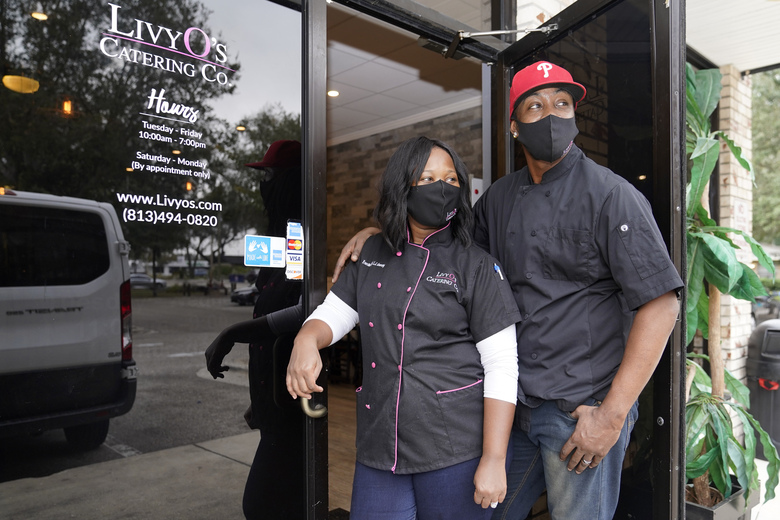 Lennise Germany, left, poses for a photograph with her husband Omar Germany, right, outside of their Livy O's Catering business, Saturday, Feb. 6, 2021, in Brandon, Fla. Livy O's Catering was awarded a contract to provide food for a pregame tailgate for 7,500 vaccinated healthcare workers invited to attend the Super Bowl Sunday in Tampa. The deal was a result of NFL Business Connect, which helps developing companies owned by women, minorities, and veterans navigate the Super Bowl procurement process. (AP Photo/Lynne Sladky)