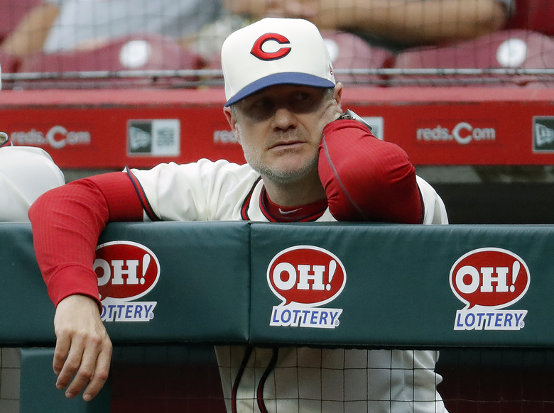 FILE – Cincinnati Reds manager David Bell watches from the dugout during the second inning of a baseball game against the Texas Rangers in Cincinnati, in this Saturday, June 15, 2019, file photo. The Cincinnati Reds will begin the 2021 season without two of last year's most important pitchers — National League Cy Young Award winner Trevor Bauer and closer Raisel Iglesias. How manager David Bell will work around those blockbuster departures is a major question as his pitchers begin throwing this week in spring training. (AP Photo/John Minchillo, File)