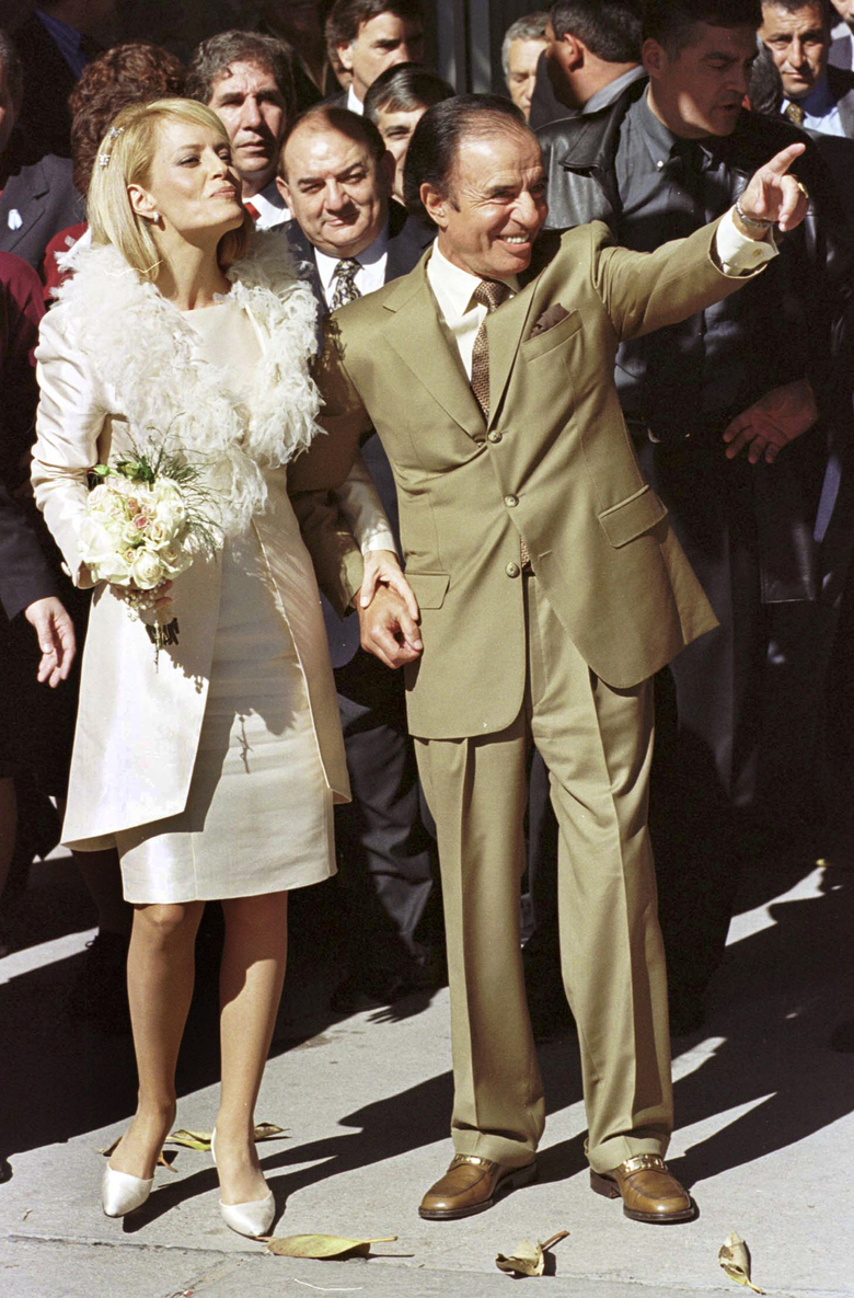 FILE – In this May 26, 2001 file photo, former Argentine President Carlos Menem and his wife Cecilia Bolocco, a former Miss Universe crown holder, stand after being married in a civil ceremony in La Rioja, Argentina. Argentine President Alberto Fernández has confirmed on Sunday, Feb. 14, 2021, that Menem, who had been ailing in recent weeks has died. (AP Photo/Julio Pantoja, File)