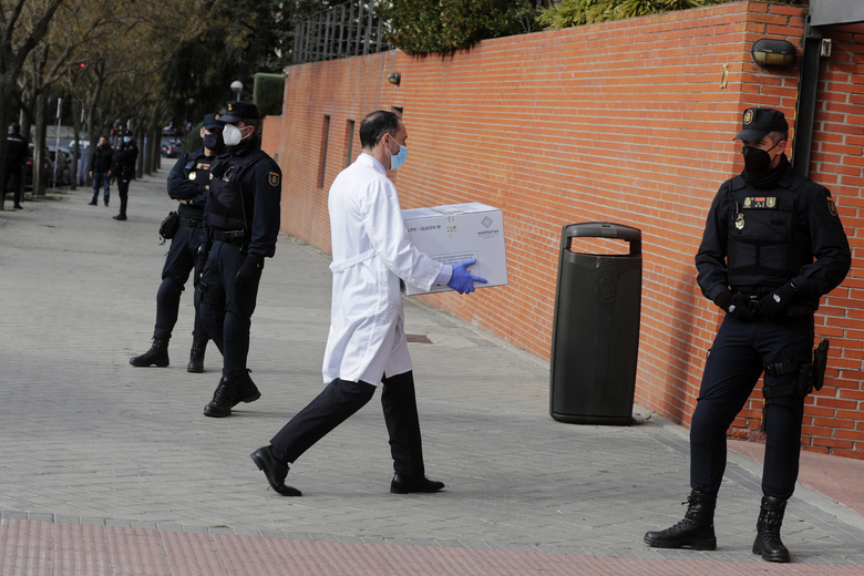 FILE – In this Sunday, Dec. 27, 2020 file photo, Police stand by the entrance of a nursing home as a box of some of the first Pfizer coronavirus vaccines arrives in Madrid, Spain. Spain plans to receive over 4.5 million doses of the vaccine over the next three months, enough it says to immunize just over 2.2 million people. The government estimates that this first phase will be enough to cover nursing home residents and workers, followed by health workers in general and people with disabilities. (AP Photo/Paul White, File)