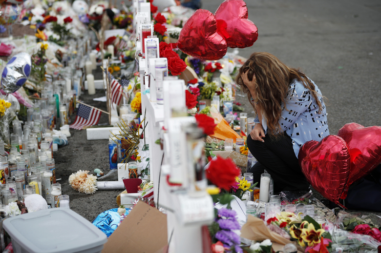 FILE – In this Aug. 6, 2019, file photo, Gloria Garces kneels in front of crosses at a makeshift memorial near the scene of a mass shooting at a shopping complex in El Paso, Texas. Twenty-three people were killed and 23 others wounded on Aug. 3, 2019, at a Walmart in the border city. Authorities say the gunman targeted Mexicans because he believed they were invading the country to vote for Democrats.  (AP Photo/John Locher, File)