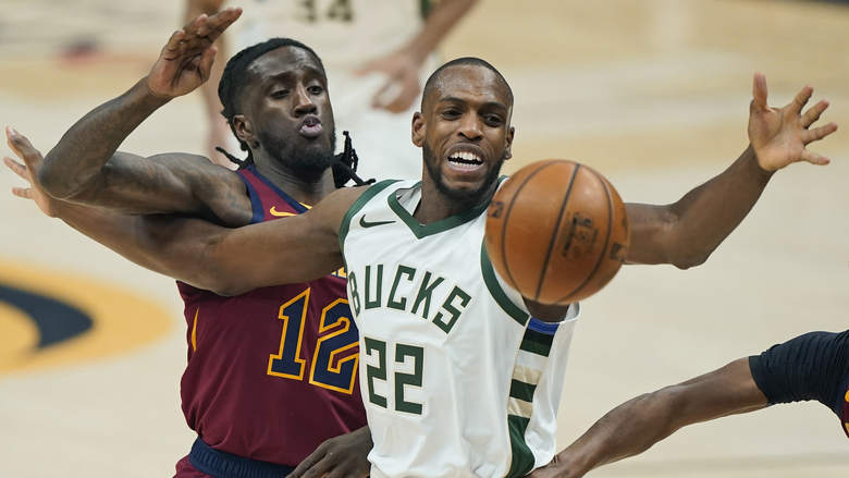 Cleveland Cavaliers' Taurean Prince (12) knocks the ball loose from Milwaukee Bucks' Khris Middleton (22) in the first half of an NBA basketball game, Friday, Feb. 5, 2021, in Cleveland. (AP Photo/Tony Dejak)