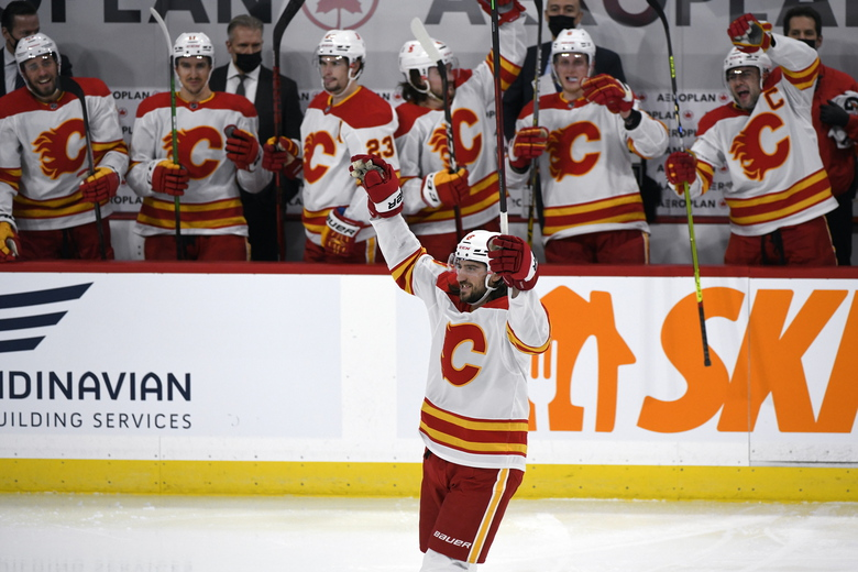 Calgary Flames' Christopher Tanev (8) celebrates his goal against the Winnipeg Jets during second-period NHL hockey game action in Winnipeg, Manitoba, Monday, Feb. 1, 2021. (Fred Greenslade/The Canadian Press via AP)