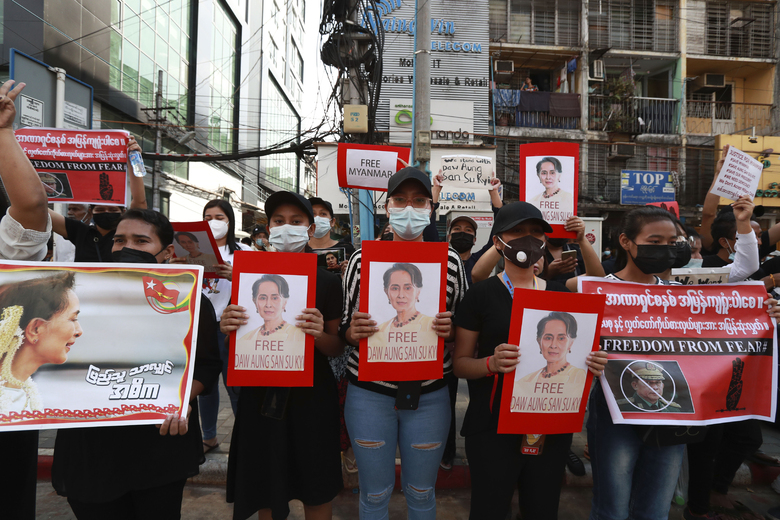 Protesters hold posters with an image of deposed Myanmar leader Aung San Suu Kyi as they march in Yangon, Myanmar on Monday, Feb. 8, 2021. Tension in the confrontations between the authorities and demonstrators against last week's coup in Myanmar boiled over Monday, as police fired a water cannon at peaceful protesters in the capital Naypyitaw. (AP Photo)
