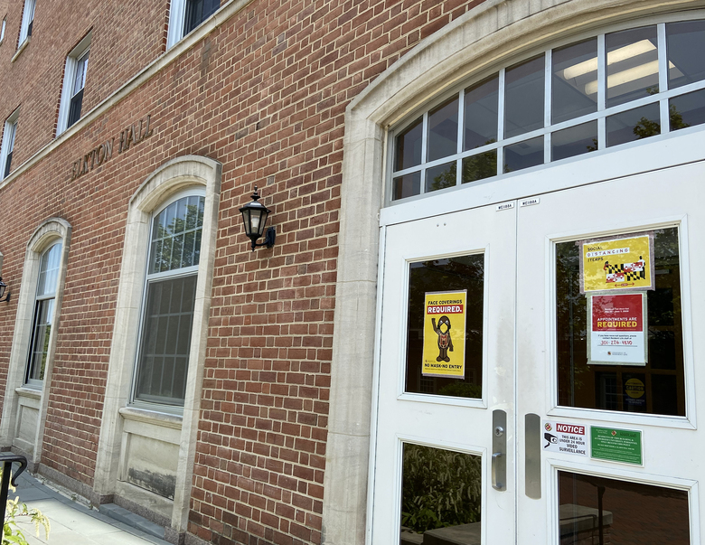 Signs plastered on Elkton Hall on the University of Maryland campus last year remind students and families to wear face coverings and practice social distancing. (Washington Post photo by Lauren Lumpkin).