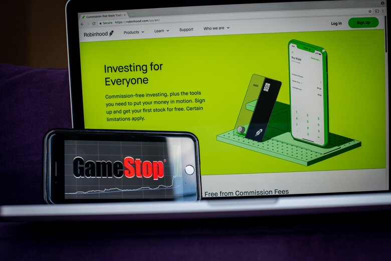 The GameStop logo on a smartphone and the Robinhood website on a laptop arranged last month in Hastings-On-Hudson, New York. (Tiffany Hagler-Geard / Bloomberg)
