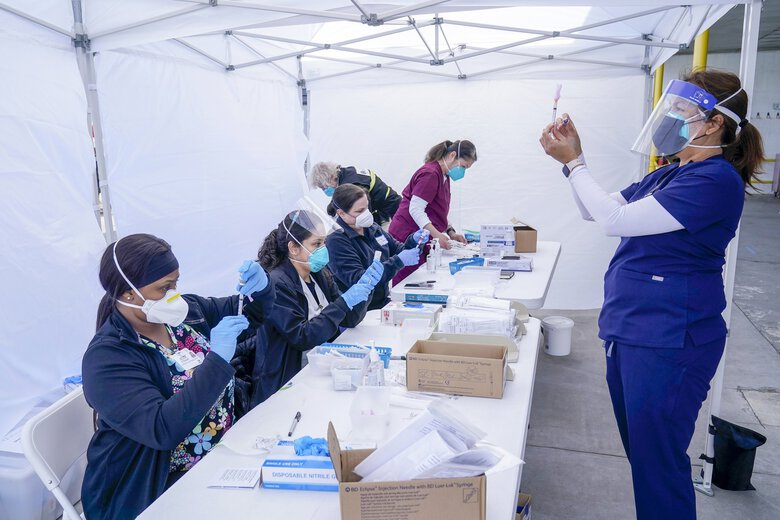 Public health nurse Dyah Moore, right, and other health care workers prepare Moderna COVID-19 vaccines for farmworkers at a County of Santa Clara mobile vaccination clinic at Monterey Mushrooms, an agricultural employer under the United Farm Workers union contract, amid the coronavirus pandemic in Morgan Hill, Calif., March 3, 2021. (Jeff Chiu / AP)