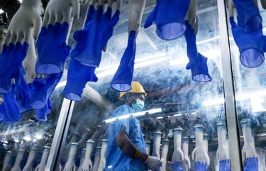 An employee monitors latex gloves on hand-shaped molds moving along an automated production line at a Top Glove factory in Setia Alam earlier in February. 775481675