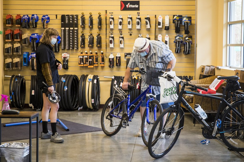John Lough, right, looks over parts for his bike with service technician Priscilla Norris at Gregg's Cycle in Green Lake. Lough is searching for a specific part to fix his wife's bike. (Amanda Snyder / The Seattle Times)