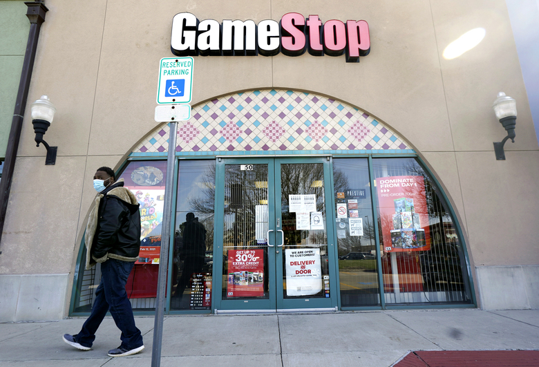 FILE – In this Jan. 28, 2021 file photo, a pedestrian passes a GameStop storefront in Dallas. A hefty tax benefit helped drive GameStop's fiscal fourth-quarter profit sharply higher, but the video-game retailer's sales declined despite a surge in its online business. The company's latest results fell short of Wall Street's expectations. (AP Photo/LM Otero, File)