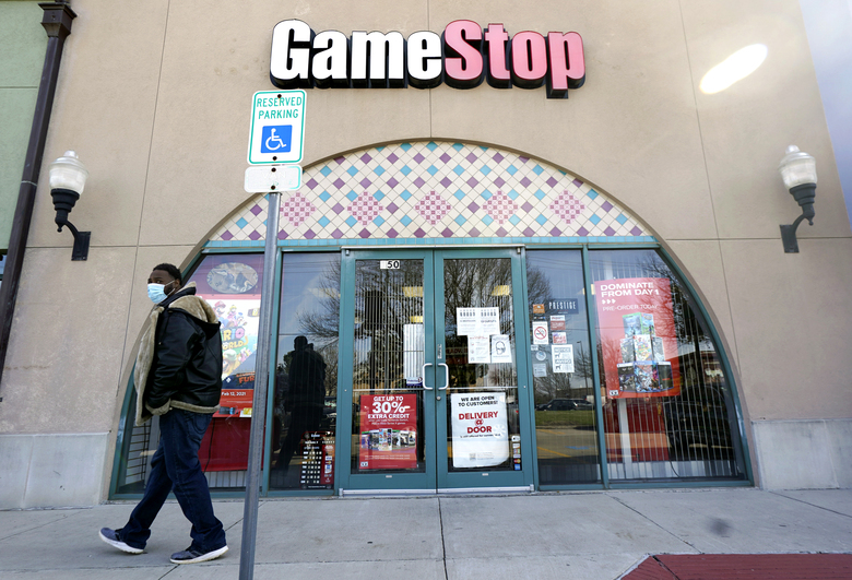 """FILE – In this Jan. 28, 2021 file photo, a pedestrian passes a GameStop storefront in Dallas. GameStop shares jumped around 12% in premarket trading Monday, March 8 after the video game retailer appointed a committee it said would aim to """"transform GameStop into a technology business.""""  (AP Photo/LM Otero, File)"""