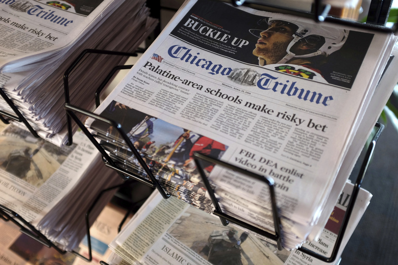 FILE – In this Monday, April 25, 2016, file photo, Chicago Tribune and other newspapers are displayed at Chicago's O'Hare International Airport, in Chicago. A group of alternative bidders is emerging, in late March 2021, for newspaper chain Tribune Publishing, which had agreed to a $630 million deal with hedge fund Alden Global Capital. (AP Photo/Kiichiro Sato, File)