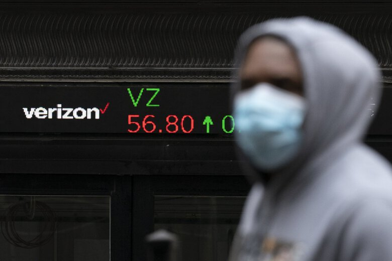 A man walks by a stock ticker displaying the cost of Verizon shares at the New York Stock Exchange Feb. 23, 2021. (Mark Lennihan / AP, file)