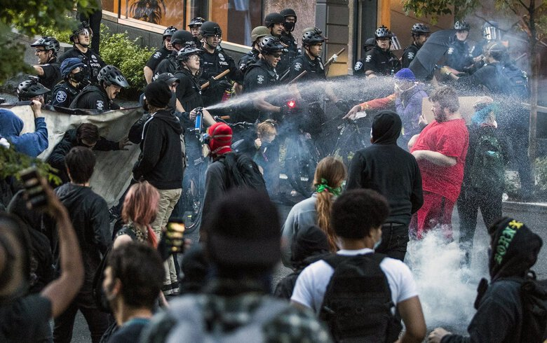 Seattle police push back demonstrators after objects were thrown at them at Fifth Avenue and Madison Street in Seattle during a march on May 29, 2020, in protest of the police killing of George Floyd. (Amanda Snyder / The Seattle Times)