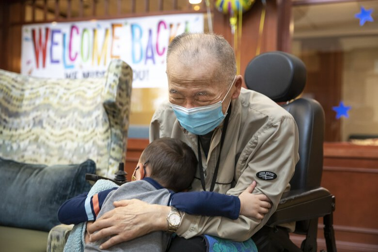 Rysic Terada, 2, gives his great-grandfather George Kozu, 94, a hug after visiting him at The Lakeshore senior-living facility Sunday March 21, 2021. It was the first time they had seen each other indoors since the start of the coronavirus pandemic.  (Bettina Hansen / The Seattle Times)