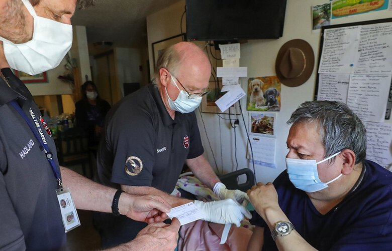 South County Fire paramedic Larry Hadland, left, hands a proof of vaccination card while emergency medical technician Kim Sharpe vaccinates Abel Cordova, 63, at his home. Cordova is unable to travel for a vaccination. (Greg Gilbert / The Seattle Times)