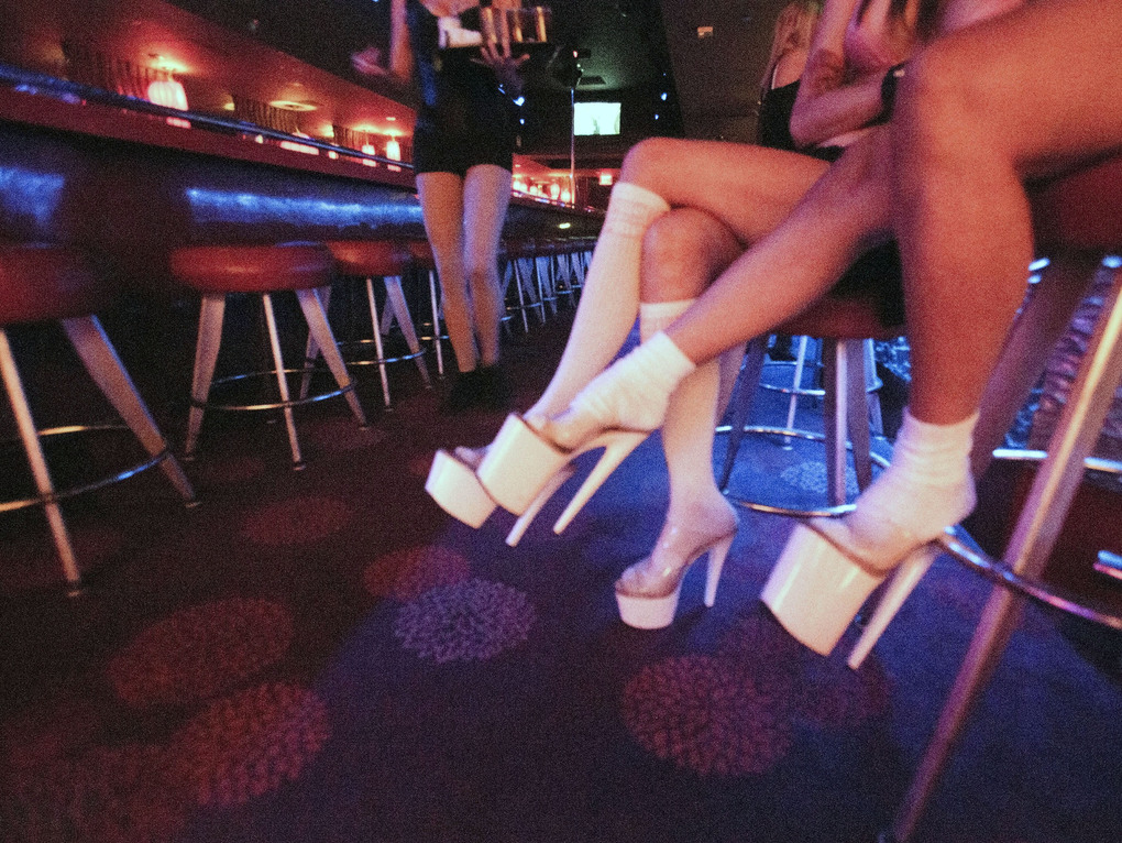 FILE – In this Tuesday, June 21, 2016 file photo, Dancers at Girls of Glitter Gulch, 20 Fremont St., sit while waiting for costumers in Las Vegas. Topless dancers can shed coronavirus restrictions next weekend in Las Vegas and get face-to-face with patrons again under rules accepted Thursday, April 22, 2021, by a state COVID-19 task force. (Jeff Scheid/Las Vegas Review-Journal via AP, File)