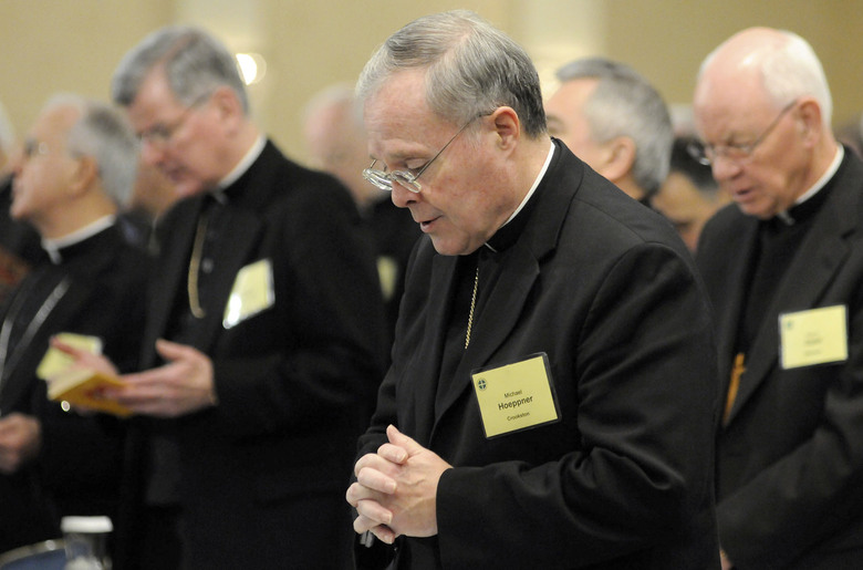 FILE – In this Monday, Nov. 10, 2008  file photo, Bishop Michael J. Hoeppner of Crookston, Minn. prays during a semi-annual meeting of the United States Conference of Catholic Bishops, in Baltimore. A Minnesota bishop who was investigated by the Vatican for allegedly interfering with past investigations into clergy sexual abuse has resigned. The Vatican said Tuesday, April 13, 2021 that Pope Francis had accepted the resignation of Crookston Bishop Michael Hoeppner and named a temporary replacement to run the dioceses. (AP Photo/ Steve Ruark, File)