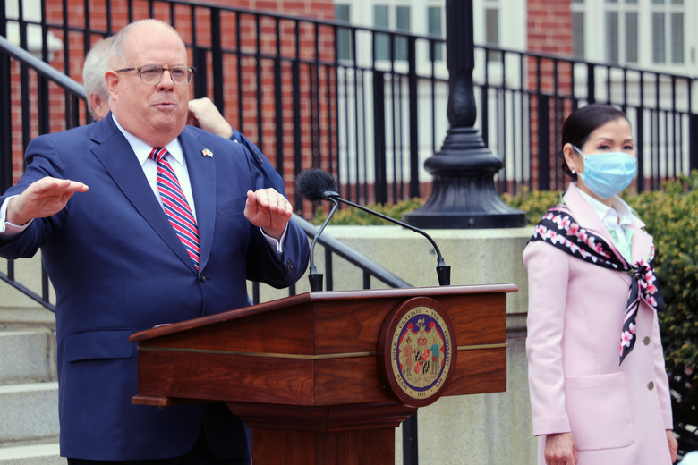 FILE – In this Monday, April 20, 2020 file photo, Maryland Gov. Larry Hogan speaks at a news conference in Annapolis, Md., with his wife, Yumi Hogan, right, where the governor announced Maryland has received a shipment from a South Korean company to boost the state's ability to conduct tests for COVID-19 by 500,000. Maryland auditors have found Gov. Larry Hogan's administration failed to follow state procurement regulations when it bought 500,000 COVID-19 tests from a South Korean company last year. The audit released Friday, April 2, 2021 also said the first batch of tests that later had to be replaced at additional $2.5 million cost had not been authorized by the U.S. Food and Drug Administration. (AP Photo/Brian Witte, File)