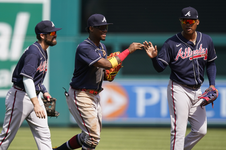 Atlanta Braves outfielders Ender Inciarte, left, Ronald Acuna Jr., and Marcell Ozuna celebrate after the first baseball game of a doubleheader at Nationals Park, Wednesday, April 7, 2021, in Washington. The Braves won the first game 7-6. (AP Photo/Alex Brandon)