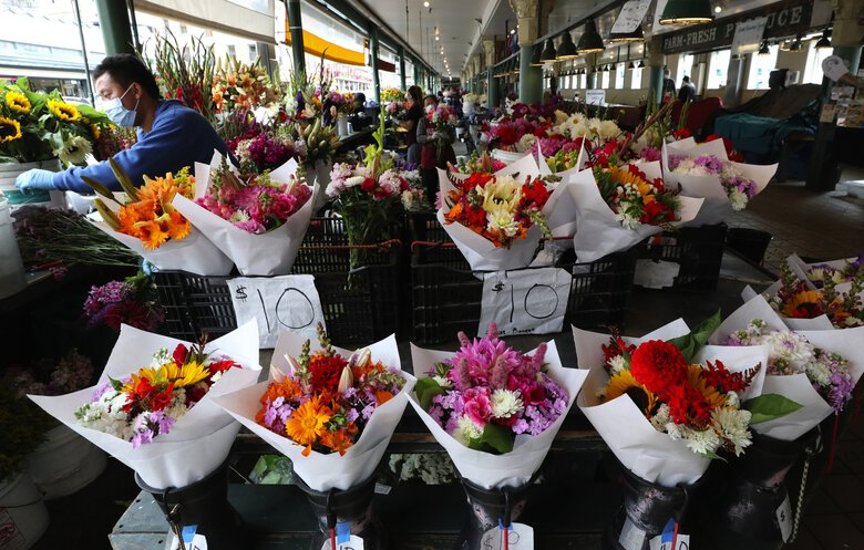 Flower vendors at Pike Place Market fill their stalls with bouquets. (Alan Berner / The Seattle Times, 2020)