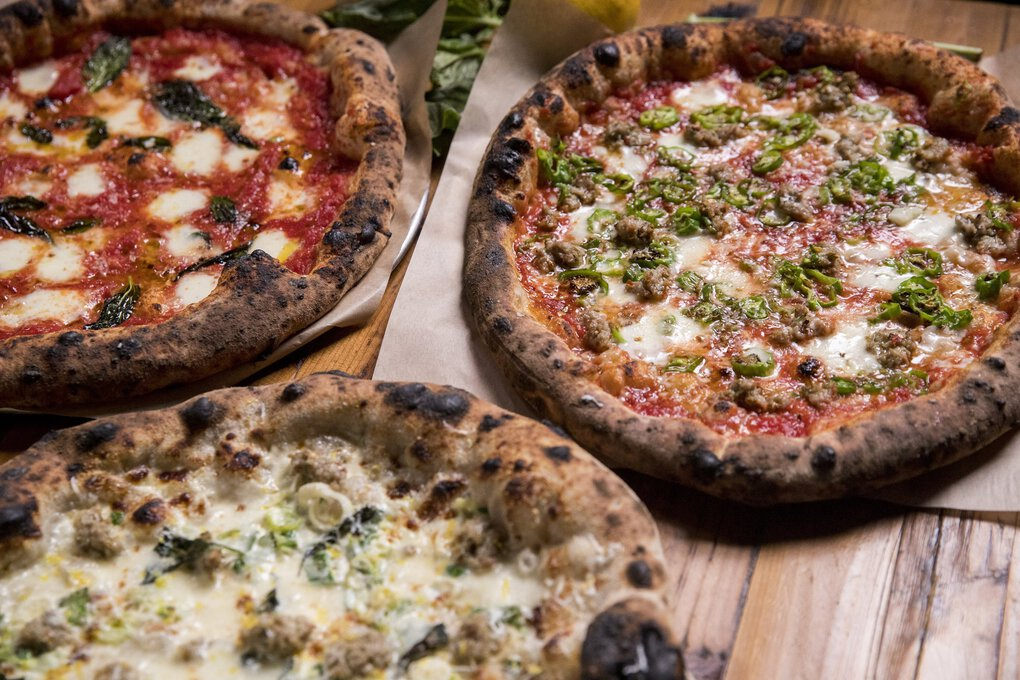 Pizza from The Carlson Block includes (from top left clockwise) the Margherita pizza, sausage and shishito pizza and green garlic cream pizza. (Amanda Snyder / The Seattle Times)