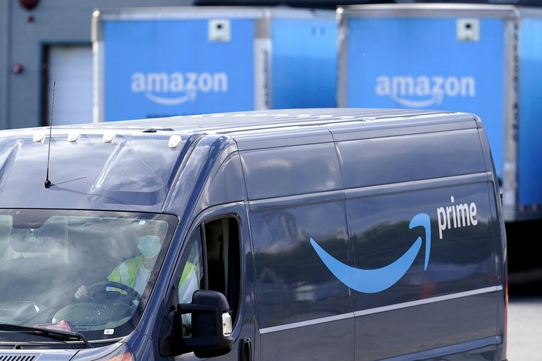Amazon is under increasing scrutiny for working conditions in its warehouses and delivery routes. Shown is a delivery van departing an Amazon warehouse. (Steven Senne / AP)