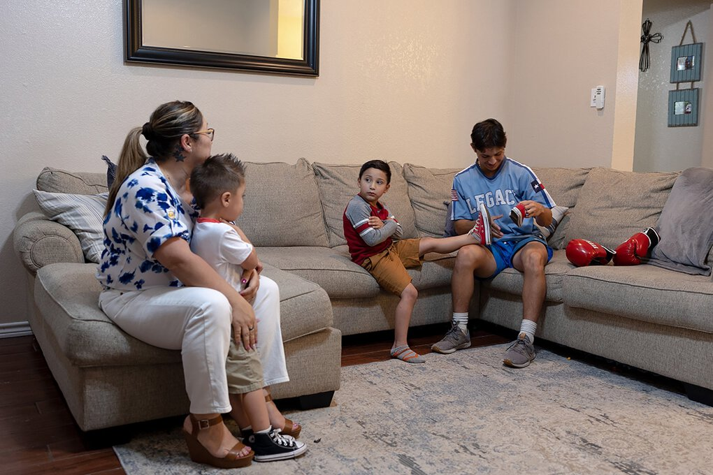 Valerie Villegas, left, holds Robert Jr. as her oldest son, Andrew Vaiz, ties Ayden's shoes. Villegas says all six of her children have been affected by the grief of losing their father and stepfather. (Scott Stephen Ball / Kaiser Health News / TNS)