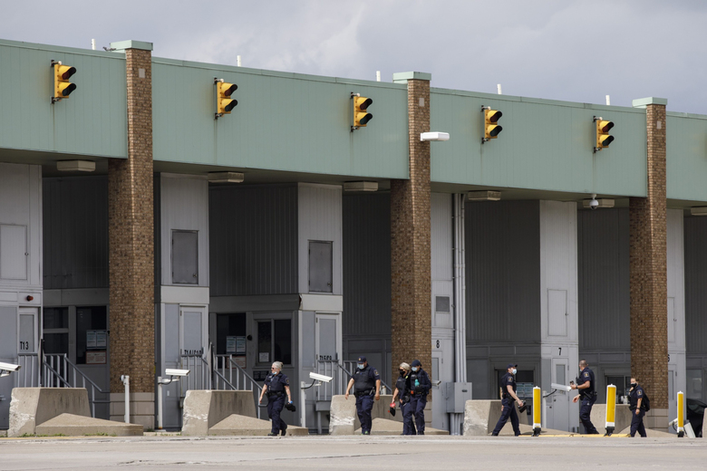 Border guards walk to their booths at the Ambassador Bridge in Windsor, Ontario, Canada, on May 26, 2021. (Bloomberg photo by Cole Burston).