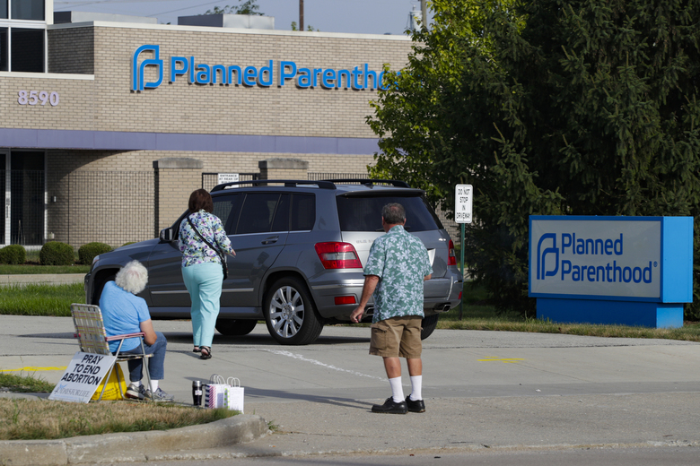 FILE – In this Aug. 16, 2019 file photo, abortion protesters attempt to handout literature as they stand in the driveway of a Planned Parenthood clinic in Indianapolis. A federal judge has blocked a new Indiana law that would require doctors to tell women undergoing drug-induced abortions about a disputed treatment for potentially stopping the abortion process. The ruling Wednesday, June 30, 2021,  came just before the so-called abortion reversal law adopted by Indiana's Republican-dominated Legislature was to take effect Thursday.  (AP Photo/Michael Conroy)