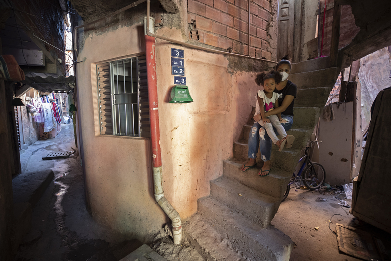 Ana Carolina Silva, who lost her job during the COVID-19 pandemic, sits with her daughter Cataleia outside her home in the Paraisopolis favela of Sao Paulo, Brazil, Monday, May 24, 2021. (AP Photo/Andre Penner)