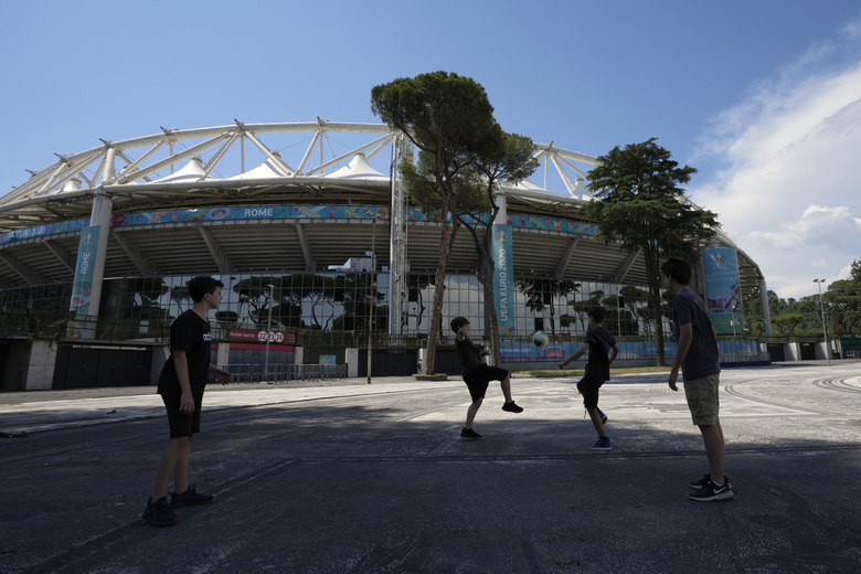 Boys play soccer in front of Rome's Olympic stadium, Wednesday, June 9, 2021. The Euro 2020 gets underway on Friday June 11 and is being played in 11 host cities across 11 countries. (AP Photo/Alessandra Tarantino)