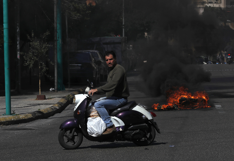 FILE – In this March 16, 2021 file photo, a man rides his scooter carrying bread as he passes in front of burning tires to block a main road, during a protest against the increase in prices of consumer goods and the crash of the local currency, in Beirut, Lebanon. on Tuesday, June 22, 2012, Lebanon's economy ministry raised the price of subsidized bread for the fifth time in a year amid the tiny country's worsening economic and financial crisis. (AP Photo/Hussein Malla, File)