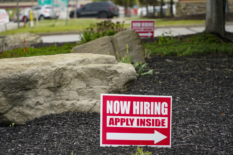 This May 5, 2021 photo shows hiring signs posted outside a gas station in Cranberry Township, Butler County, Pa. The number of Americans applying for unemployment benefits dropped last week,  reported Thursday, June 24, a sign that layoffs declined and the job market is improving.  (AP Photo/Keith Srakocic)