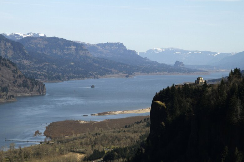 The Columbia River flows past the Vista House on Crown Point at right, with Beacon Rock visible in the distance near Corbett, Ore. The Columbia River Treaty between the U.S. and Canada is decades old and needs updating, Northwest lawmakers have written President Joe Biden. Changes to the pact on water use, power production and flood prevention have been in the works for years.  (Don Ryan / AP, File)