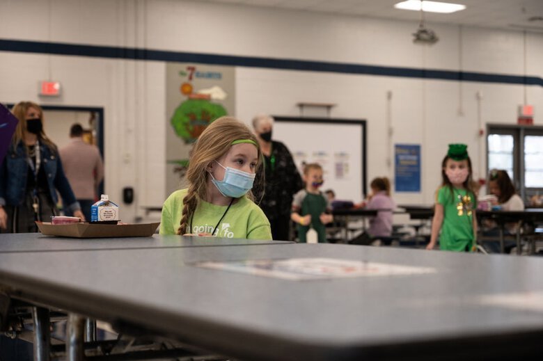 A masked student sits in the socially distanced cafeteria during lunch at Medora Elementary School in Louisville, Kentucky, in March 2021. (Jon Cherry/Getty Images/TNS)