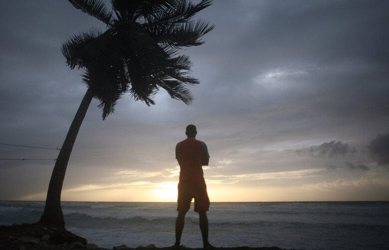 A man look out at the beach as a storm approaches in Barahona, Dominican Republic. (Ricardo Arduengo / The Associated Press)