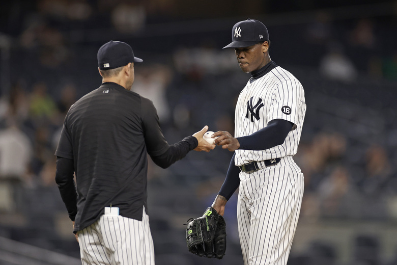 New York Yankees relief pitcher Aroldis Chapman hands the ball to manager Aaron Boone as he is removed during the ninth inning of the team's baseball game against the Los Angeles Angels early Thursday, July 1, 2021, in New York. The Angels won 11-8. (AP Photo/Adam Hunger)