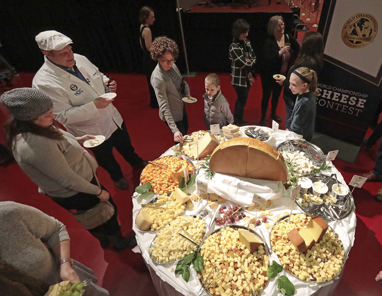 FILE – In this March 5, 2020 file photo, visitors to the Cheese Champion event of the World Championship Cheese Contest sample offerings from an array of international producers during the gathering at Monona Terrace in Madison, Wis. A bill being heard by a state Assembly committee would make colby, which was created in Wisconsin more than 100 years ago, the official stage cheese. (John Hart/Wisconsin State Journal via AP, File)