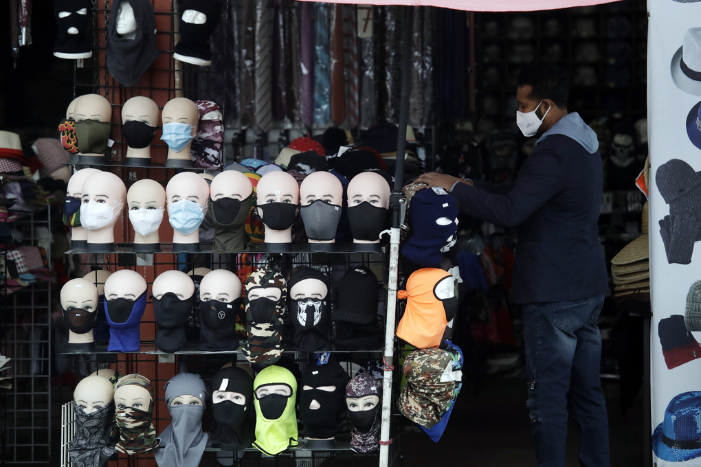 FILE – In this Friday, March 20, 2020, file photo, a merchant displays masks for sale in Los Angeles. Retail analysts expect mask sales will get another jolt after the Centers for Disease Control and Prevention late Tuesday, July 27, 2021, changed course on some masking guidelines, recommending that even vaccinated people return to wearing masks indoors in parts of the U.S. where cases of the coronavirus are surging. (AP Photo/Marcio Jose Sanchez, File)