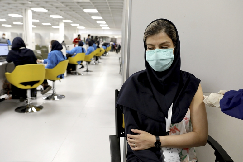 FILE – In this May 17, 2021 file photo, a medical worker receives the Sinopharm coronavirus vaccine at the Iran Mall shopping center in Tehran, Iran. Iran announced on Sunday, July 4, 2021, that it was reimposing coronavirus restrictions on major cities as the spread of the highly contagious delta variant spurs fears of another devastating surge in the nation. (AP Photo/Ebrahim Noroozi, File)